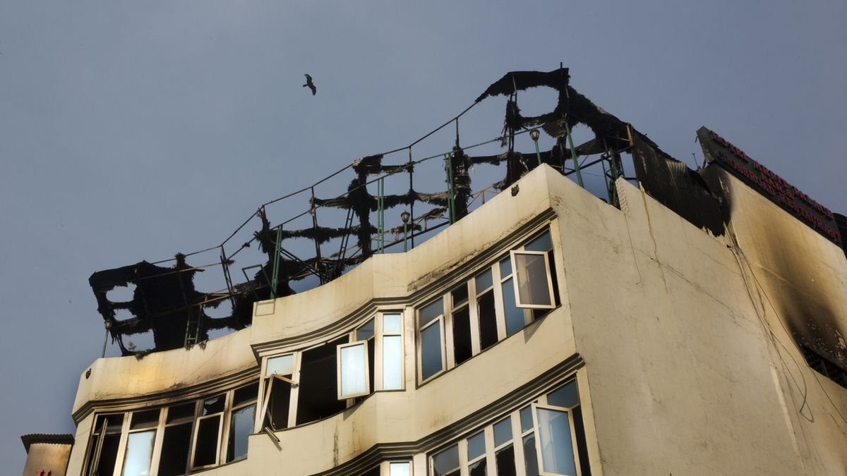 A bird flies above the Arpit Palace Hotel where an early morning fire killed more than a dozen people in the Karol Bagh neighborhood of New Delhi, India, Tuesday, Feb.12, 2019. (AP Photo/Manish Swarup)