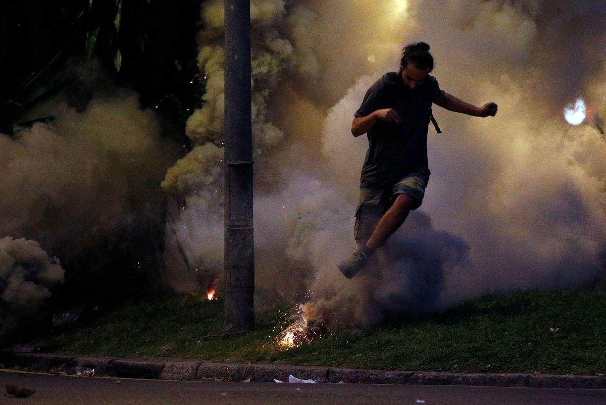 Demonstrant utíká před oblakem slzného plynu