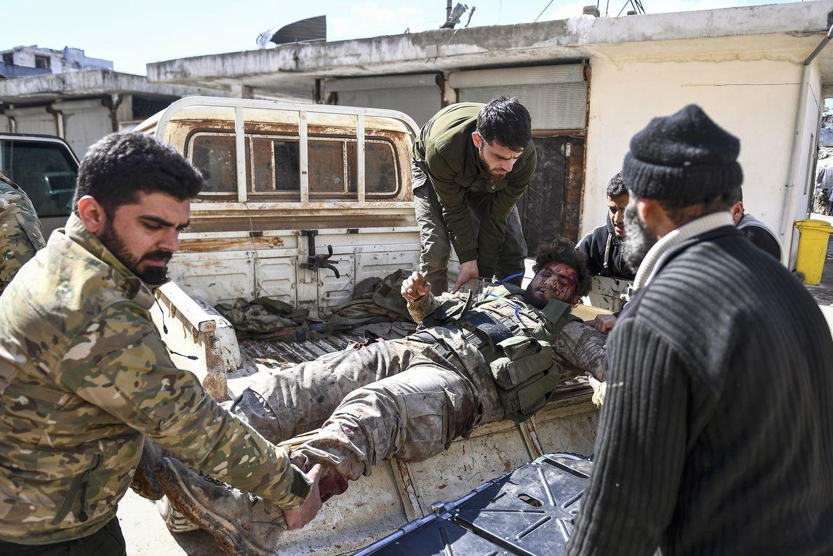 Tureckem podporovaní syrští vzbouřenci nakládají zraněného spolubojovníka na korbu pick-upu.