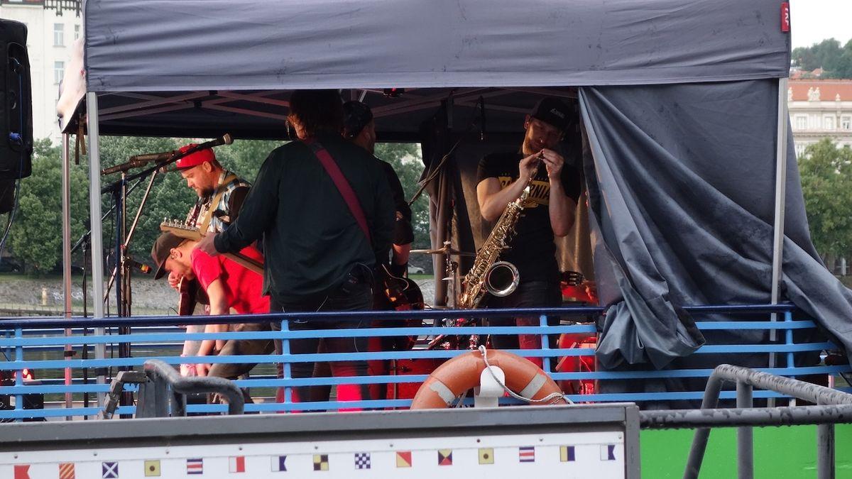 Kapely hrají na lodi plující na Vltavě. UDG vystoupili dvakrát pro sto lidí