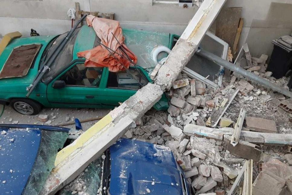 Výbuchem poničený dům a auta