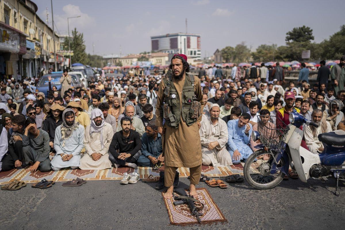 Bojovník Tálibánu před klečícími věřícími v Kábulu