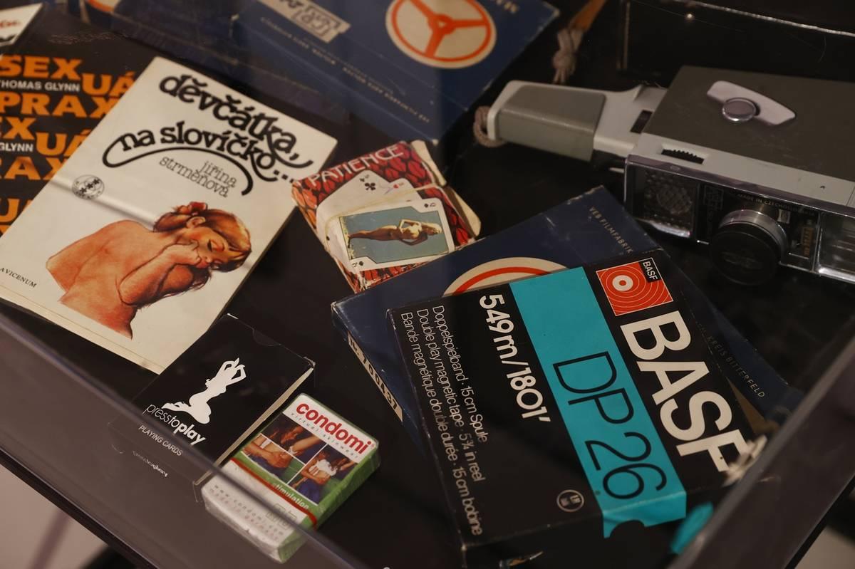 Nechybí ani ukázka dobových kondomů, nahaté kanasty a ikonická příručka sexuální výchovy normalizačních puberťaček Děvčátka, na slovíčko...