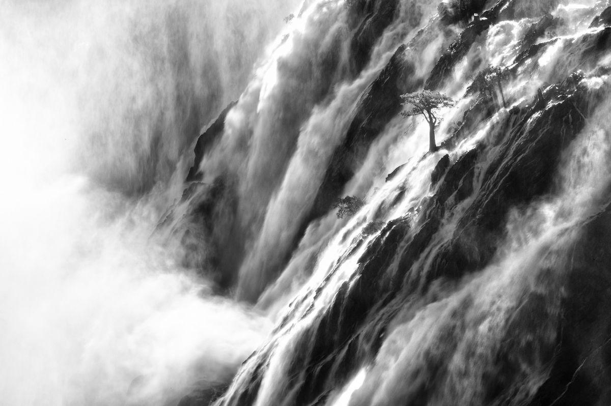 Mocné vodopády Ruacana (Namibie) - Doporučeno v kategorii Příroda. Řeka Kunene protéka Angolou až k namibijským hranicím, kde padá ze skal v podobě mocných vodopádů. Mladé baobaby rostou ze skal a kolem nich se řítí masy vody.