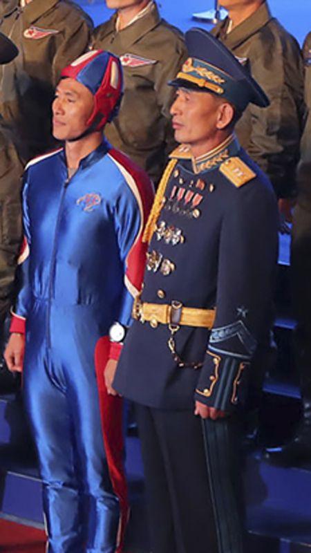 Detail muže v podivném obleku na oficiální fotografii při obranné konferenci KLDR