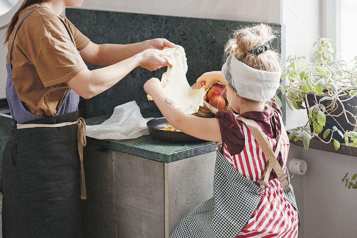 Kuchyňské zástěry s nastavitelnými řemínky vyhovují dětem, drží totiž krok s jejich růstem.