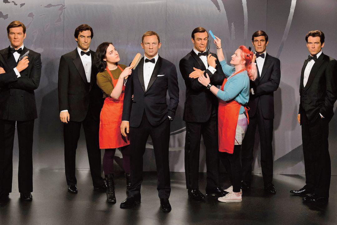 Roger Moore a Sean Connery již zemřeli, všichni Bondové se proto sejdou leda jako voskoví, v tomto případě v Londýně. Zleva Moore, Dalton, Craig, Connery, Lazenby a Brosnan.