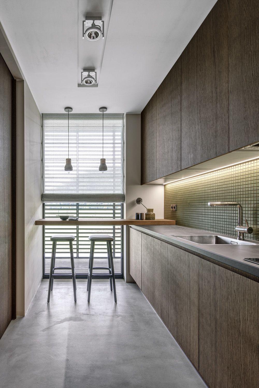 Nábytek kuchyňské linky z tmavě mořené dubové dýhy doprovází obklad ze zelené mozaiky. Dřez a baterie nesou značku Blanco.