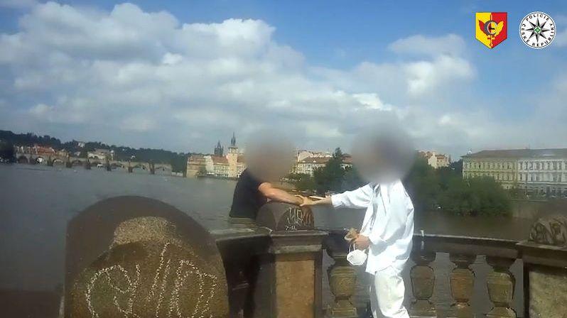 Muž v Praze chtěl skočit z mostu, dívka v bílém ho držela za ruku do zásahu policie