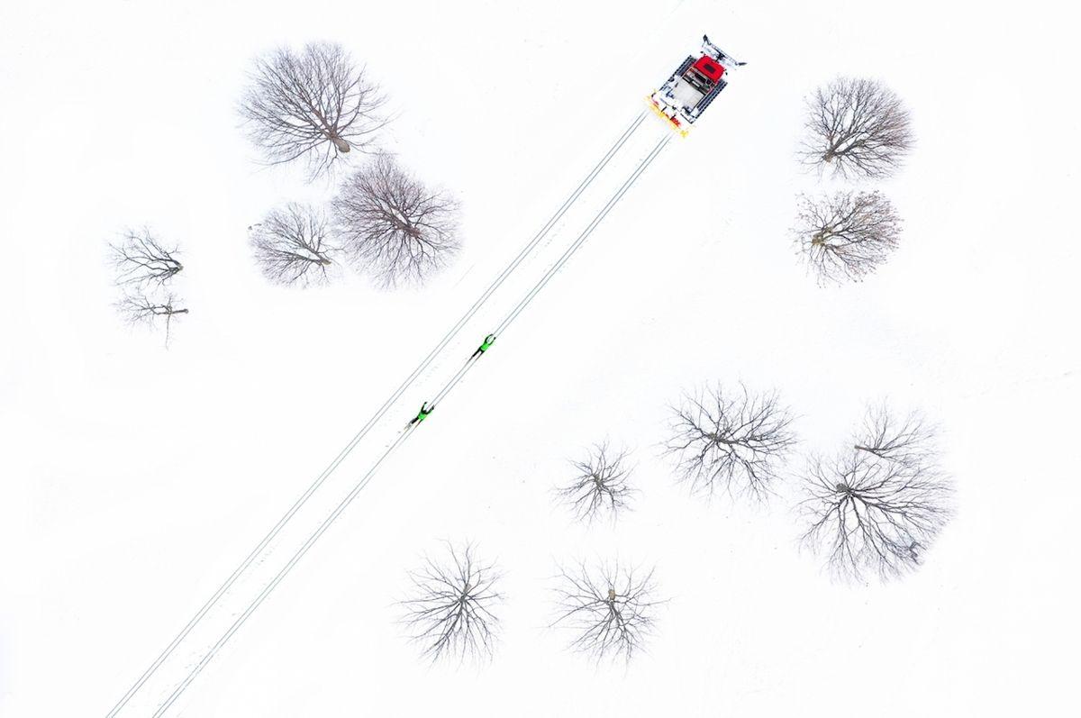 Následuj mě (Německo) - Finalista kategorie Sport. Fotka vznikla v německém Bernau. Sněžný pluh razil novou běžeckou trasu a dva běžkaři byli přímo za ním.  Snímek byl přeexponován, aby vynikl pocit pomíjivosti, kterou scéna vzbuzuje.